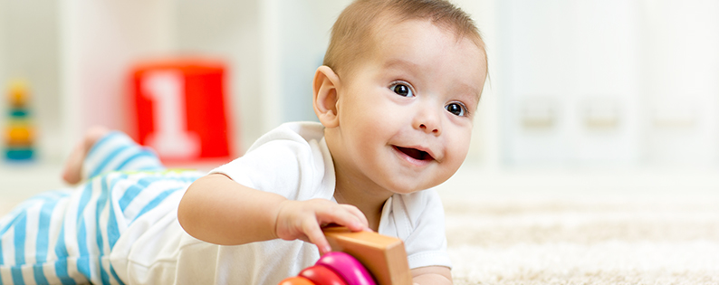 smiling baby boy playing with a stacking ring toy